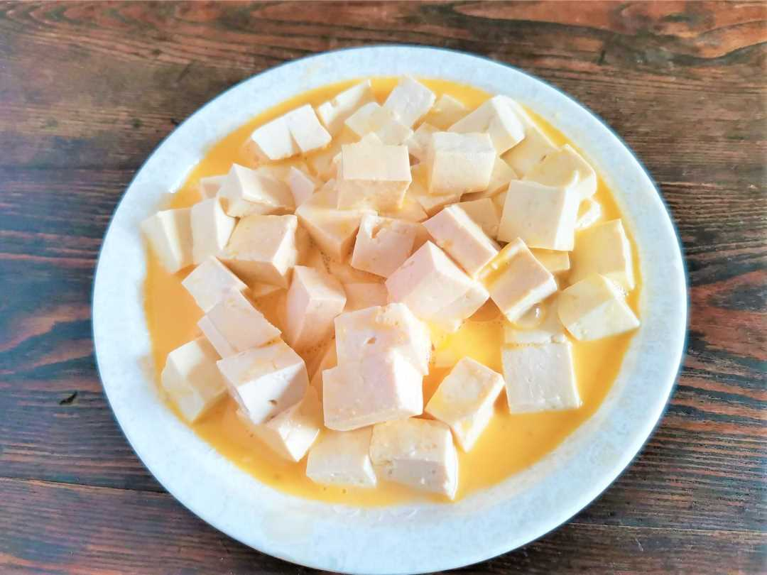 Cut the tofu into small pieces, put them on a plate, knock the eggs into the plate, mix well