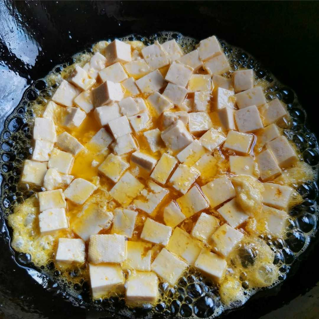 Add oil to the pot to heat, pour tofu and fry