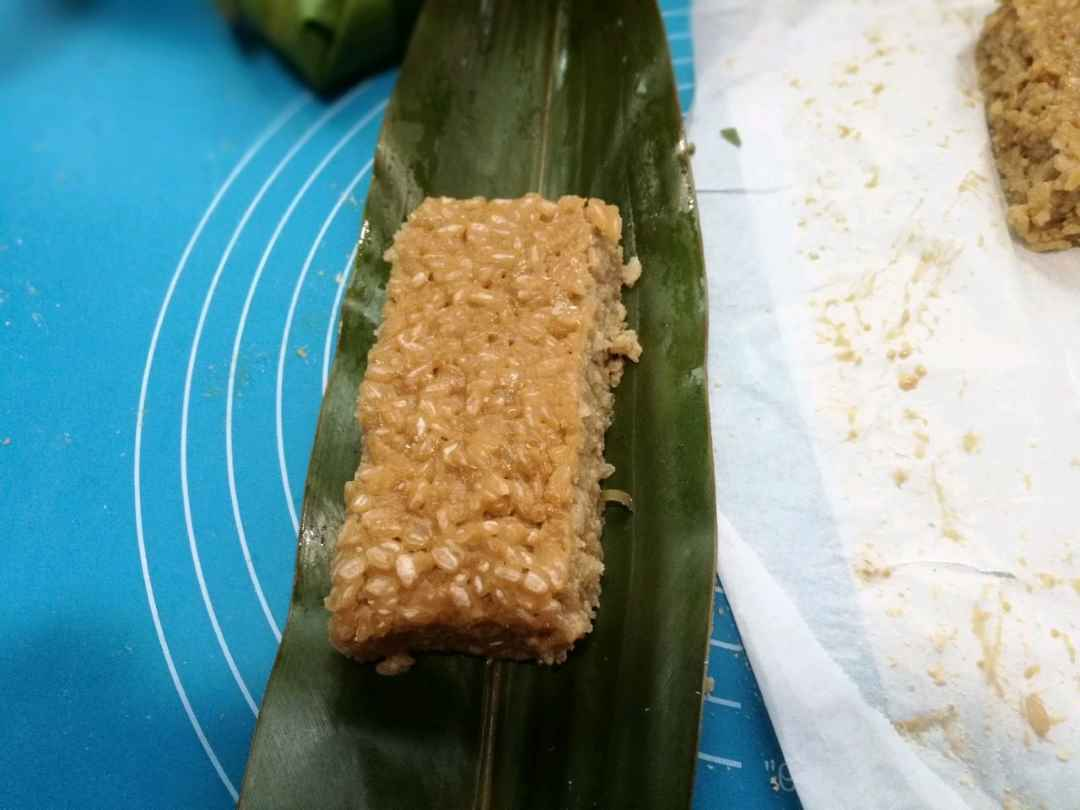 Take a piece of yellow rice cake and place it in the middle of the leaves