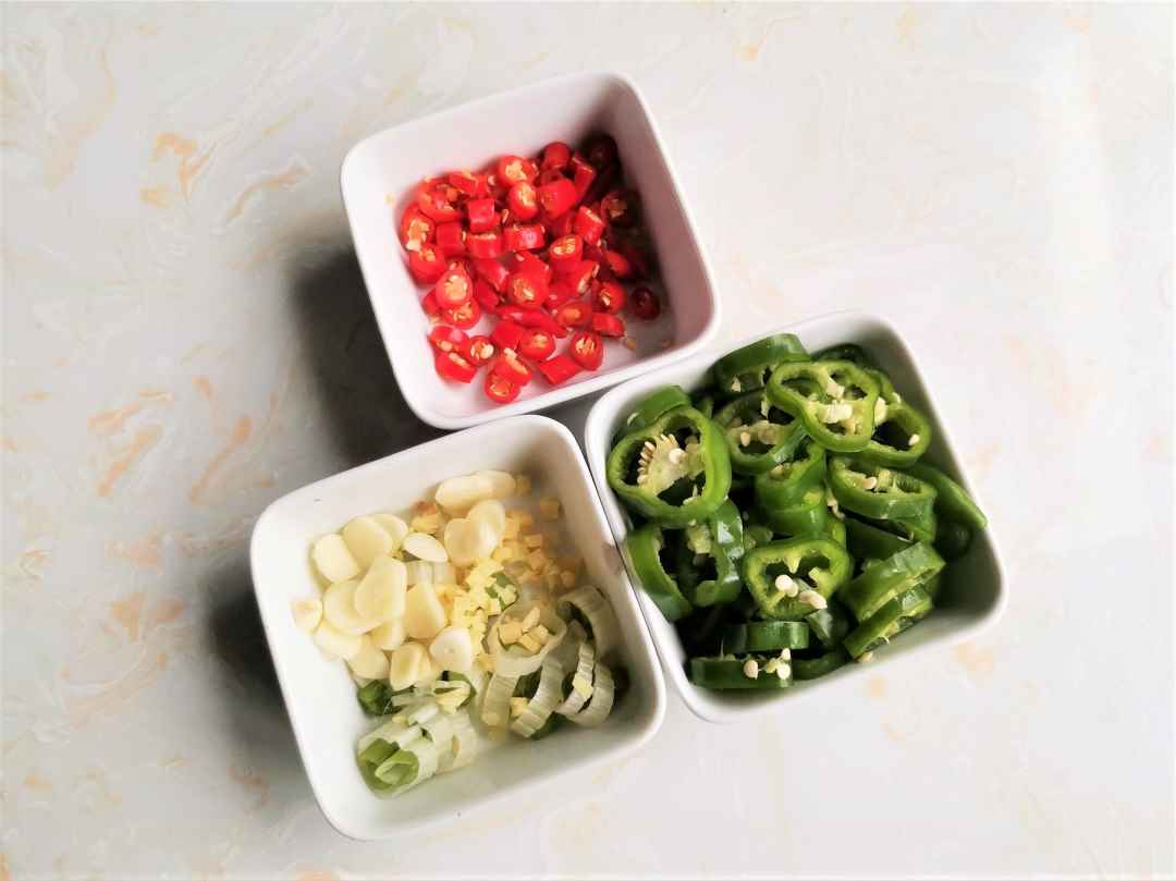 Cut green peppers and chili peppers into chili rings, and prepare green onions, garlic, and ginger.