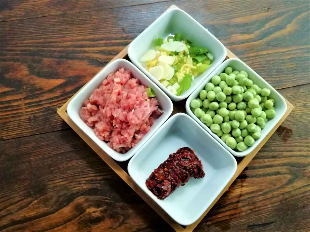 Peel the peas, mince the pork, slice the garlic, chop the green onions and ginger.